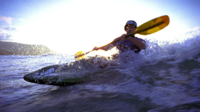 side boat point of view man in kayak in ocean riding wave + stabilizing with oar / hawaii - pagaiare video stock e b–roll