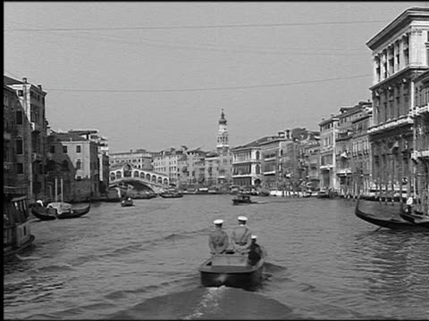b/w 1930 boat point of view on grand canal with boat traffic / rialto bridge (ponte di rialto) in background / venice, italy - ponte stock videos & royalty-free footage