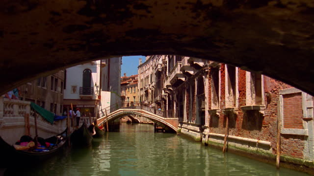 boat point of view on narrow canal with buildings and under footbridges / venice, italy - boat point of view stock videos & royalty-free footage