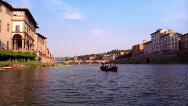 pan boat point of view passing boat with four people in it on arno river / florence, italy - florence stock videos and b-roll footage