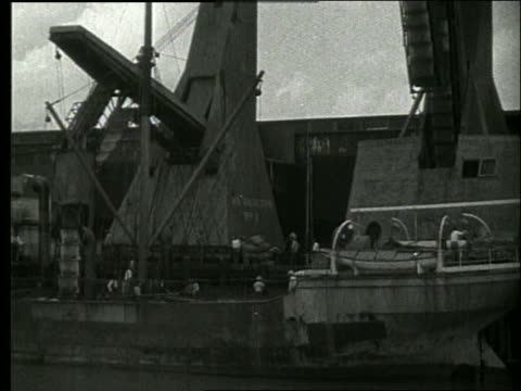 b/w boat point of view past cargo being loaded onto ship / dock workers / no sound - 1910 stock videos & royalty-free footage