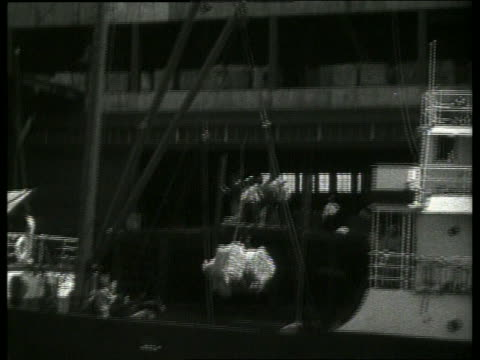 b/w boat point of view past cotton being lifted from ship at dock / 1910 / dock workers / new orleans / no sou - 1910 stock-videos und b-roll-filmmaterial