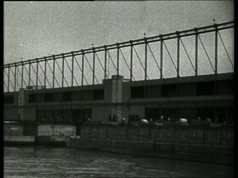 b/w boat point of view past cotton warehouse on dock / new orleans / 1910 / no sound - 1910 stock-videos und b-roll-filmmaterial