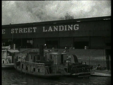 b/w boat point of view past docked boats and warehouse / new orleans / 1910 / no sound - new orleans stock videos & royalty-free footage