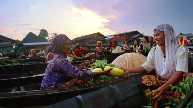 vídeos de stock e filmes b-roll de boat point of view past female vendors exchanging fruit and vegetables at floating market on river / indonesia - indonesia