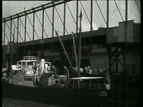 b/w boat point of view past ship at dock and warehouse / new orleans / 1910 / no sound - 1910 stock-videos und b-roll-filmmaterial