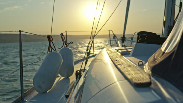 day on a sailboat - boat point of view while arriving the coast line while sunrise. - sailing stock videos & royalty-free footage