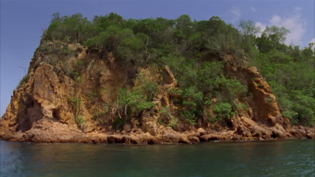 Boat point of view wide shot passing promontory on Pacific coastline / Costa Careyes, Mexico
