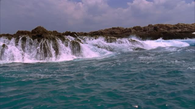 boat point of view wide shot waves crashing onto rocky coastline / costa careyes, mexico - rocky coastline stock videos & royalty-free footage