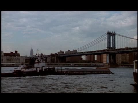 a boat pushes a barge on the east river near the brooklyn bridge. - brooklyn bridge stock-videos und b-roll-filmmaterial