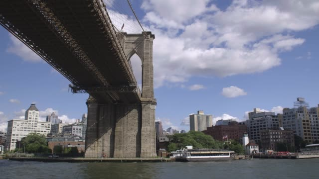 boat ride around manhattan.  a boat drifts under the brooklyn bridge. - river east stock videos & royalty-free footage