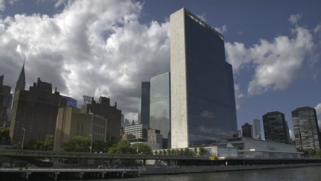 boat ride drifts past the un building - united nations stock videos & royalty-free footage