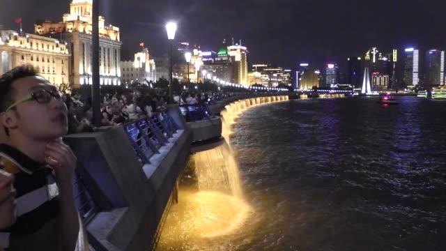 Boat ride on Huangpu River and tourists at the Bund at night in Shanghai