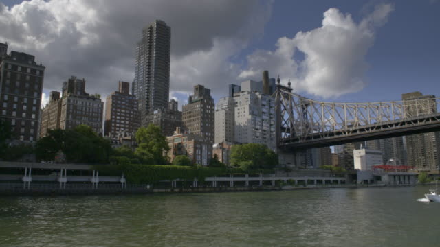boat ride past apartments and the queensboro bridge on the upper east side of manhattan. - queensboro bridge stock videos & royalty-free footage