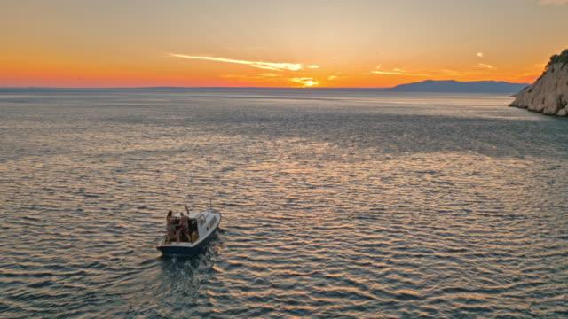 AERIAL Boat riding along coastline at sunset