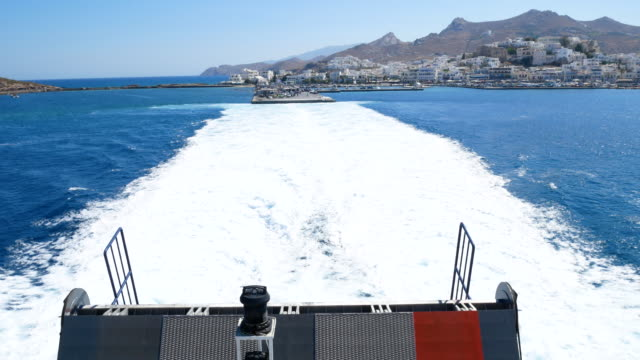 boat riding at aegean sea with naxos island background, 4k resolution. - naxos greek islands stock videos & royalty-free footage