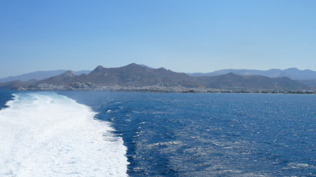 boat riding at aegean sea with naxos island background, 4k resolution - water's edge stock videos & royalty-free footage