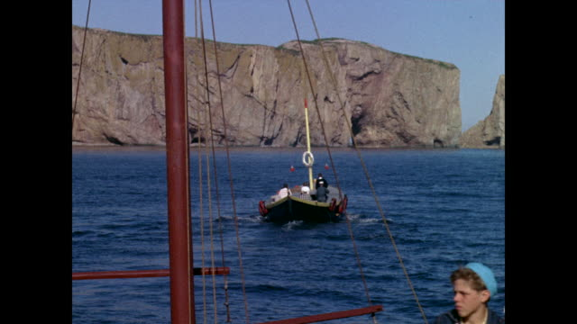 boat sailing away from dock towards perce rock quebec flag in foreground. - atlantic ocean stock videos & royalty-free footage