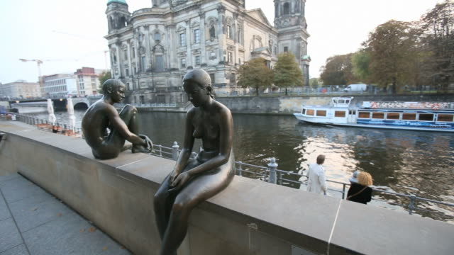 Boat sailing in the canal next to Museum island and Berliner dom (Berlin Cathedral), with human bronze statues in foreground