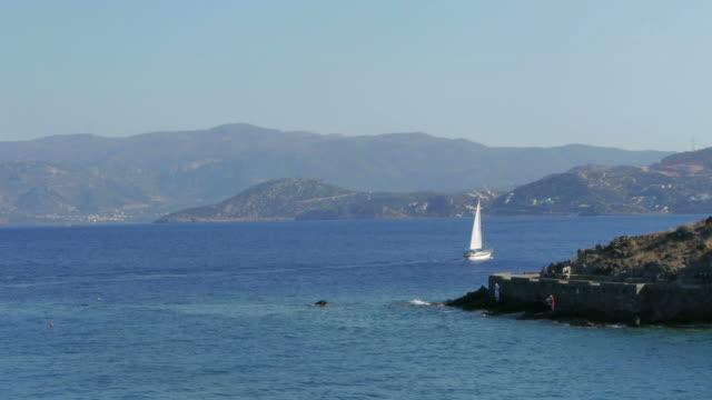 boat sailing on agios nikolaos on crete, greece. - spoonfilm stock-videos und b-roll-filmmaterial