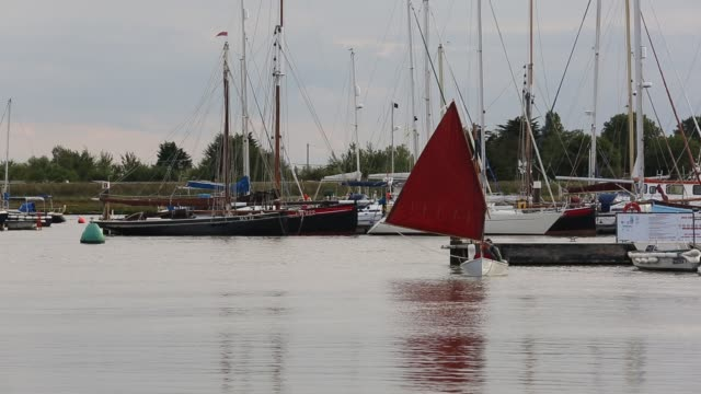 a boat sailing passed a group of sailing boats moored at brightlingsea in essex united kingdom on september 3 2015 - sailing boat stock videos & royalty-free footage