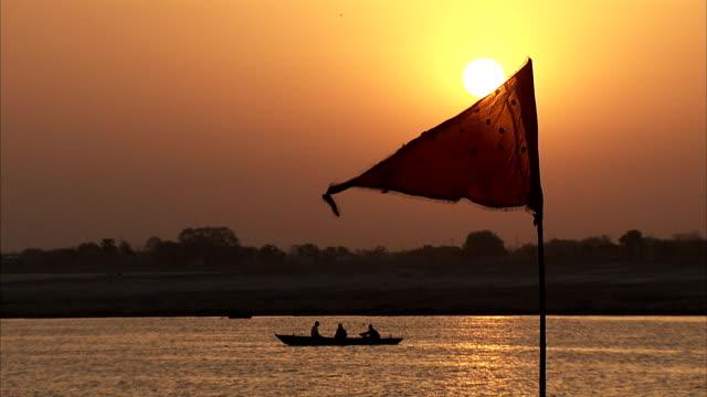 vídeos y material grabado en eventos de stock de a boat sails behind a waving flag by the river ganges at sunset. - contraluz