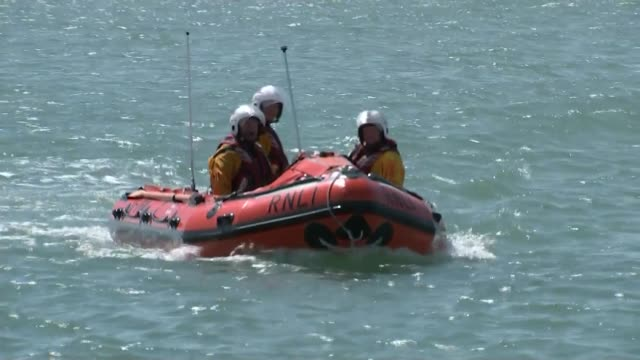 one dead and two missing england west sussex shoreham ext rnli lifeboat house rnli volunteers in inflatable rescue boat wide shot of helicopter... - イギリス海峡点の映像素材/bロール