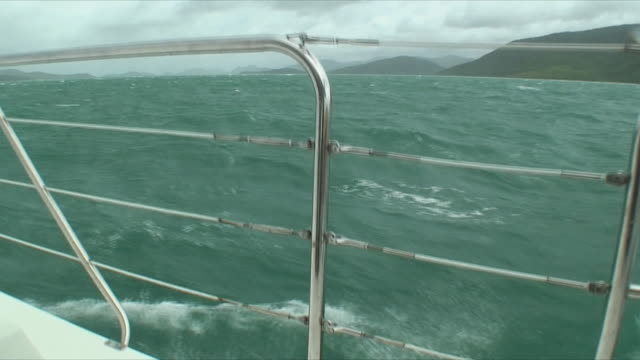 POV Boat swimming through water, boat's railing in foreground, Whitsunday Islands, Queensland, Australia