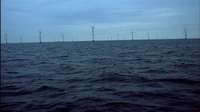 long shot boat pov toward wind turbines spin in baltic sea, nysted offshore wind farm, denmark. - ostsee stock-videos und b-roll-filmmaterial