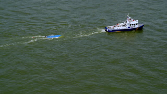aerial nypd boat tows object in river - towing stock videos & royalty-free footage