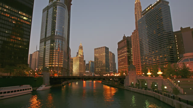 vídeos y material grabado en eventos de stock de time lapse medium shot boat traffic under bridge on chicago river from day to night, chicago, illinois - edificio wrigley
