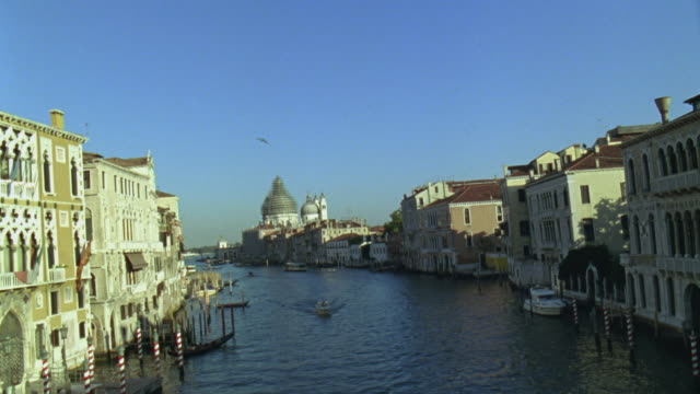 HA WS Boat traveling in canal with Santa Maria della Salute in background / Venice, Italy