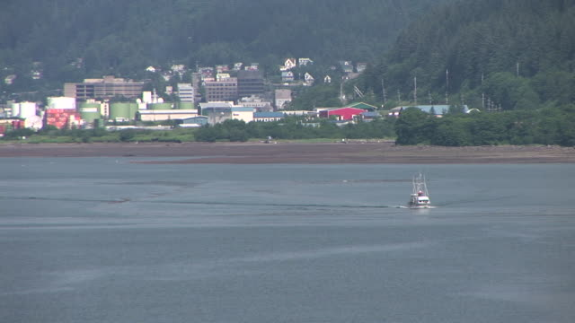 ws, boat traveling in sea, port of juneau in background, alaska, usa - juneau stock videos and b-roll footage