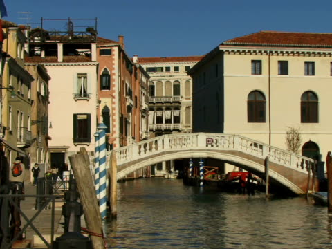 ws boat traveling on canal as pedestrians cross over footbridge / venice, italy - besichtigung stock-videos und b-roll-filmmaterial