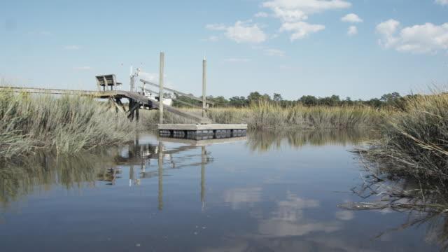 ws slo mo pov boat traveling on marsh river / charleston, south carolina, usa - carolina del sud video stock e b–roll