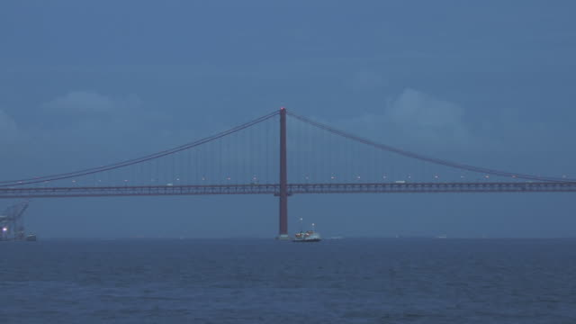 ws zo boat traveling on tagus river at dusk below april 25th bridge near monument to the discoveries / lisbon, portugal - 4月25日橋点の映像素材/bロール