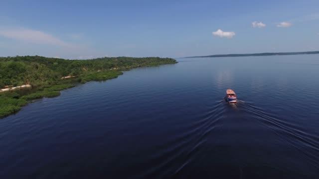 ブラジル・アマゾンのリオ・ネグロ上空を移動するボート - アマゾン熱帯雨林点の映像素材/bロール