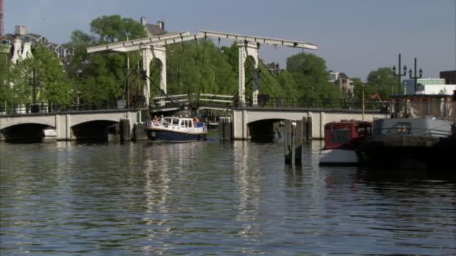 ws boat traveling under magere brug on amstel river / amsterdam, netherlands - okänt kön bildbanksvideor och videomaterial från bakom kulisserna