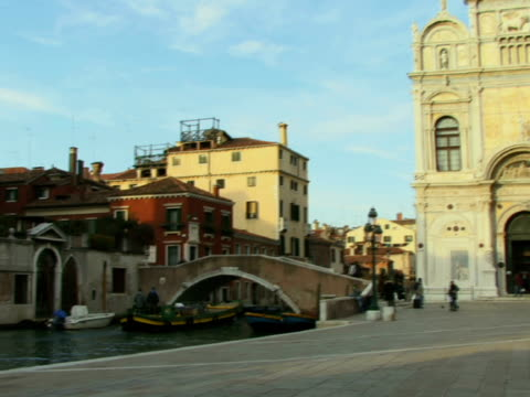 ws pan boat traveling under ponte cavallo as tourists walk past scuola grande di san marco - ponte点の映像素材/bロール