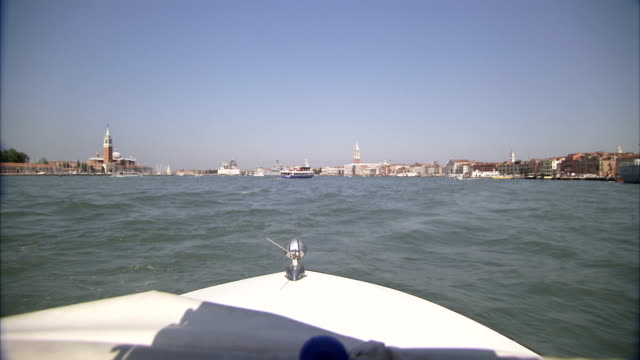 a boat travels across a lagoon towards venice. - dondolarsi video stock e b–roll