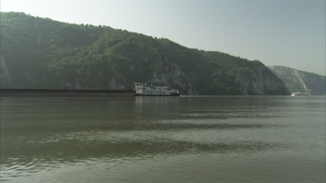 a boat travels by a mountain on the danube river. - river danube video stock e b–roll
