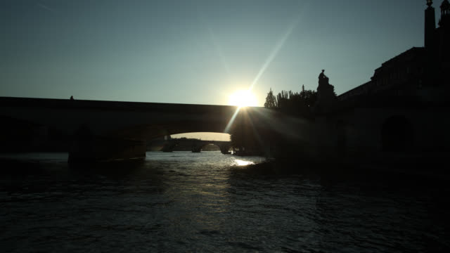 A boat travels on the River Seine during golden hour.