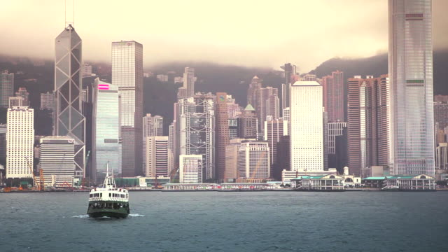A boat travels through a body of water in Hong Kong with a view of the city seen in the background.