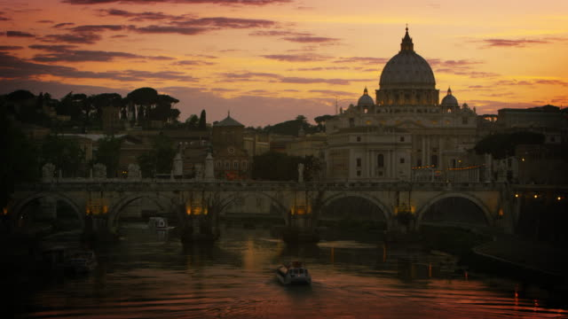 a boat travels under the ponte sant'angelo at dusk. dome of st. peter's basilica  in the background - サンタンジェロ橋点の映像素材/bロール