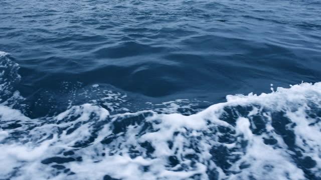 Boat wake on the blue ocean sea