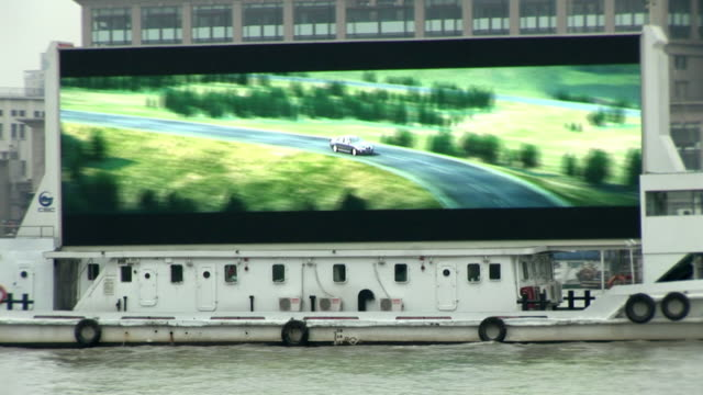 MS, Boat with large screen broadcasting different advertisements on Huangpu River, Shanghai, China