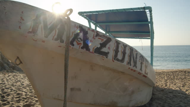 boat with mazunte banner parked at beach, oaxaca state, mexico. establishing shot - banner sign stock videos & royalty-free footage