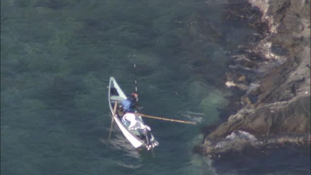 A boater pushes a pole into the Sea of Japan near the coast of the Shakotan Peninsula.