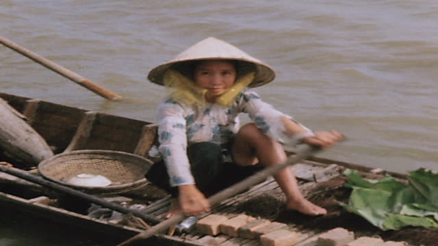 ts boater wearing non la hat paddling sampan / vietnam - sampan stock videos & royalty-free footage
