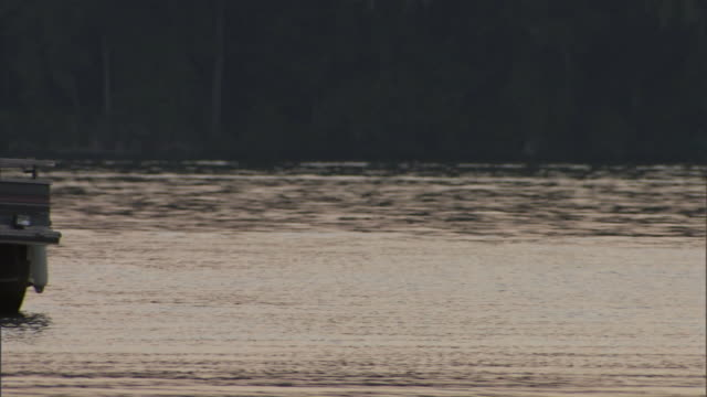 vidéos et rushes de boaters cross a lake on a pontoon boat. - chapeau de paille